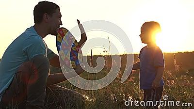 O pai segura dardos nas mãos e dá cinco ao filho - movimento lento, pôr do sol filme