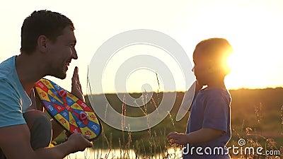 O pai segura dardos nas mãos e dá cinco ao filho, pelo que acertou no alvo vídeos de arquivo
