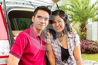 O par asiático está feliz na parte dianteira o carro