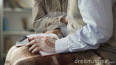 O par envelhecido abre o álbum de fotografias no regaço para olhar junto imagens, reminiscente video estoque