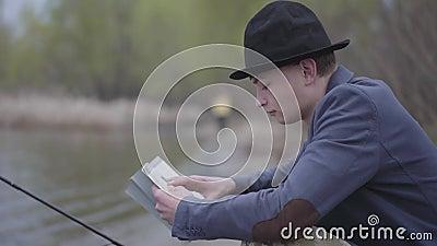 O pescador à moda do retrato em um revestimento e em um tampão de campo senta-se perto de um rio e lê-se um livro ou pontas da pe vídeos de arquivo