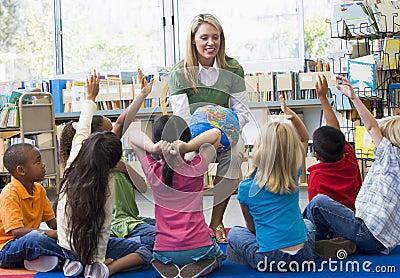 O professor e as crianças com mãos levantaram na biblioteca