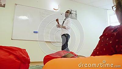 O professor negro africano americano explica o material para o estudante sentado em uma cadeira confortável Vista inferior de dif filme