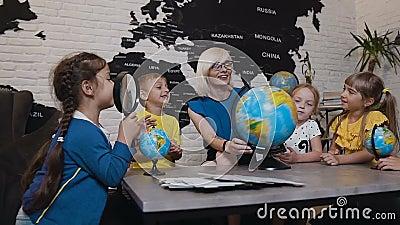 O professor que ajuda à escola caçoa no globo da leitura na sala de aula da geografia na escola primária Um professor atrativo é video estoque
