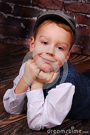 O rapaz pequeno elegante em um tampão e as lãs investem