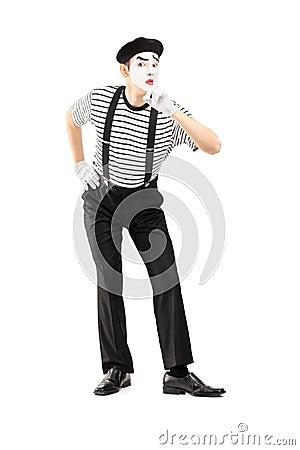 O retrato completo do comprimento de um homem mimica o artista que gesticula o silêncio