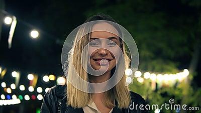 O retrato de uma menina bonita em um casaco de cabedal preto e a blusa branca que está na noite estacionam Luz de um café filme