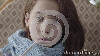 O retrato do adolescente envolveu no len?o morno que guarda um term?metro em sua boca e mede a temperatura A menina video estoque