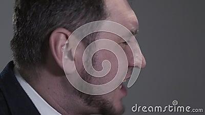 O retrato do perfil do homem em um terno de negócio que lendo uma batida, cante ou rapidamente diga a algo quando ativamente video estoque