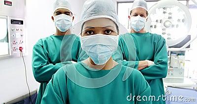 O retrato dos cirurgiões e da enfermeira que estão com braços cruzou-se na sala de operação video estoque