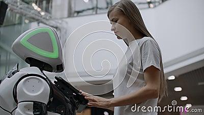 O rob? olha a menina. Intelig?ncia artificial. Tecnologias rob?ticos modernas. O robô olha para a garota com filme