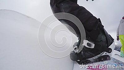 O Snowboarder calça luvas e começa-as inclinar-se A câmera é fixa a bordo video estoque