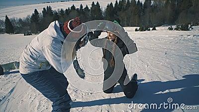 O Snowboarder ou o esquiador e o fotógrafo fazem a sessão de foto no tiro meados de da estância de esqui vídeos de arquivo