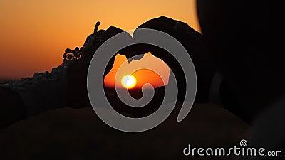 O Sol está nas mãos mulher e homem fazendo sinais cardíacos com mãos em frente a um lindo pôr do sol no horizonte equipe video estoque