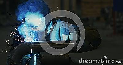 O soldador na máscara de solda, na roupa de funcionamento na fábrica, solda a tubulação na sala da fábrica video estoque