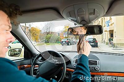O taxista está olhando no espelho de condução