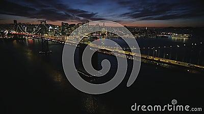 O tiro aéreo fascinante da skyline do centro de aço grande de golden gate bridge San Francisco iluminou a arquitetura da cidade c video estoque