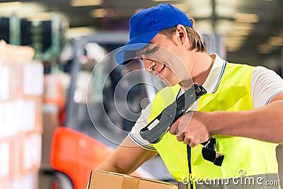 O trabalhador faz a varredura do pacote no armazém da transmissão