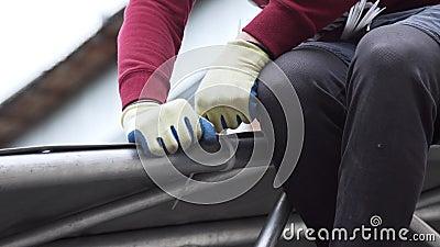 O trabalhador fixa o encerado cinzento à estrutura de alumínio com os pinos plásticos brancos vídeos de arquivo