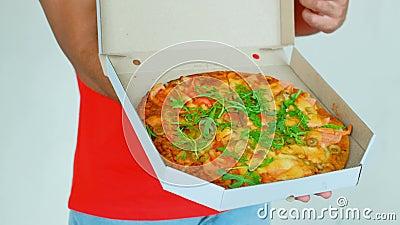 O trabalhador novo consider?vel da entrega no uniforme vermelho est? guardando uma pizza, est? olhando a c?mera e est? sorrindo,  filme