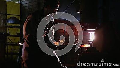 O trabalhador opera-se com a máquina metalúrgica automatizada em uma fábrica do forjamento do metal vídeos de arquivo