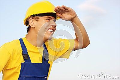 O trabalhador que olha para a frente, cobrindo eyes do sol