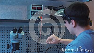 O trabalhador usa a unidade da fonte de alimentação do laboratório para investigar o mau funcionamento filme