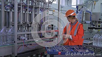 O trabalho pesado do técnico da mulher na planta, na fêmea de sorriso forte no workwear e no capacete repara profissionalmente a  video estoque