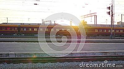 O trem está cruzando uma estrada de ferro após ter saido do estação de caminhos-de-ferro vídeos de arquivo