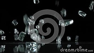 O vidro quebrado cai ao assoalho Fundo preto Movimento lento filme