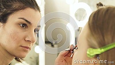 O visagiste da mulher que usa a escova cosmética para aplicar-se compõe na mulher bonita da cara da pele no estúdio dos cosmético video estoque