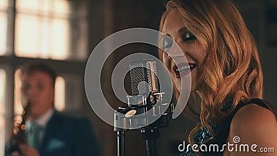 O vocalista no vestido de incandescência executa na fase no microfone Estilo retro elegance video estoque
