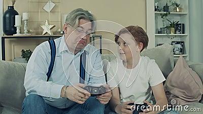 O vovô está explicando ao avô como jogar o console filme