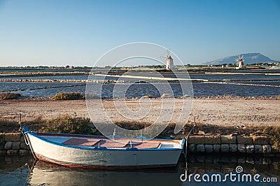 Oar boat and windmills in a restful seascape
