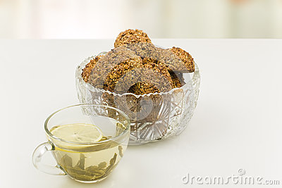 Oatmeal cookies in a crystal vase and  cup of  tea