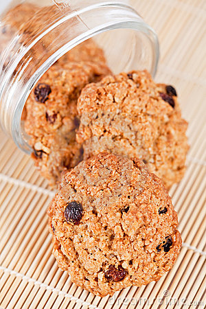 Oatmeal raisin cookies coming out of a glass jar