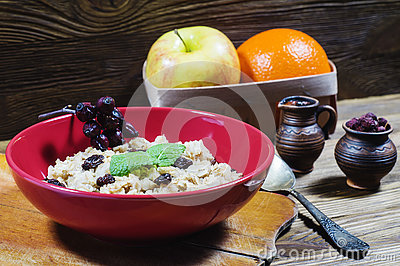 Oatmeal with raisins, branch of wild rose and mint. Stock Photo