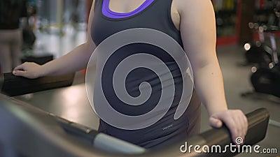 Obésité de combat de femme dans le gymnase, s'exerçant sur le tapis roulant, séance d'entraînement pour le corps sain banque de vidéos