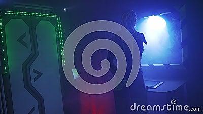 Obcy statek kosmiczny, kobieta w metalu opancerzeniu z długimi dreadlocks, jest trwanie i patrzejący w porthole, 4k zbiory