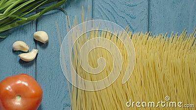 Oberste Ansicht: rohe Spaghetti, die auf den blauen Holztisch fallen stock video footage