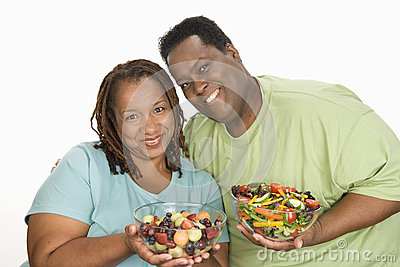 Obese Couple Holding Bowl Of Salad