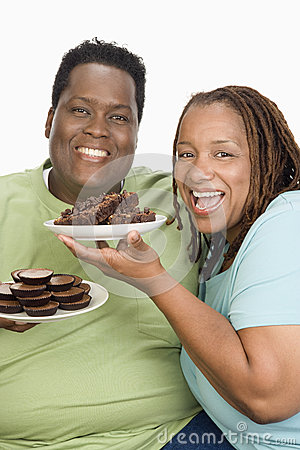 An Obese Couple Holding Plates Of Pastries