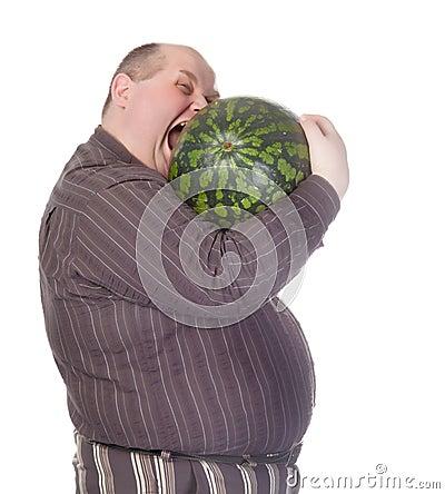 Obese man biting a watermelon