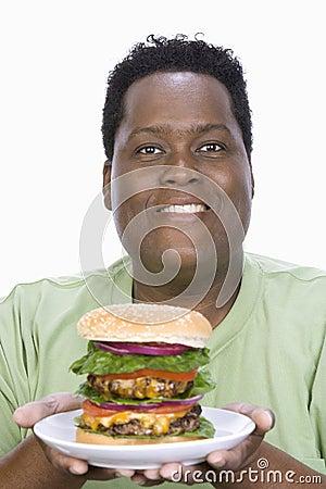 An Obese Man Holding Hamburger