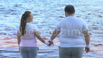 Obese man taking girlfriends hand, couple enjoying beautiful view of river. Stock footage stock video