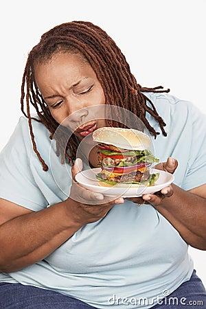 Obese Woman Looking At Burger