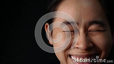 Occhi chiusi per una donna che piange con un sorriso sullo sfondo nero archivi video