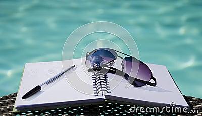 Occhiali da sole e penna su un blocco note
