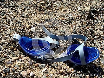 Occhiali di protezione di nuoto sulla sabbia