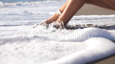 Oceaangolven die meer dan gelooide vrouwelijke voeten wassen Benen van sexy meisje het liggen gouden zand op overzees strand en h stock videobeelden